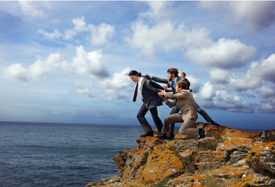 Businessmen pulling colleague from cliff